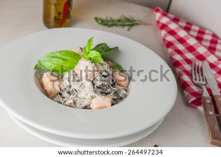 Black pasta with salmon in cream sauce, italian cuisine decorated with basil on round white plate - stock photo