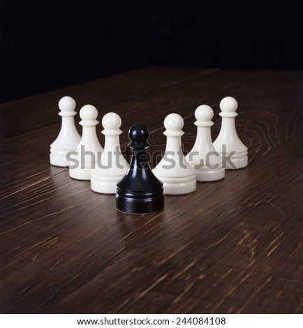 Black pawn in focus on a background white pawns on a wooden table. - stock photo