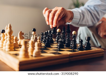 Black pawn in the hand of an experienced Chess players - stock photo