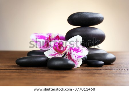 Black pebbles with orchid on wooden table
