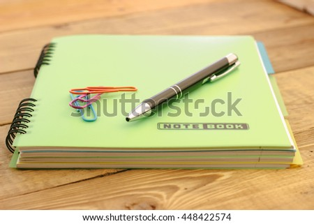 black pen and paper clips on the closed notebook lying on a wooden table - stock photo
