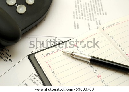 Black pen on planner with business documents in background, signifying concepts such as office and business, planning for the new year, financial budget and work related objects