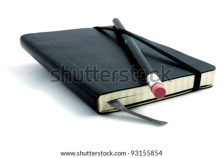 Black pen with pink rubber on black leather moleskin notebook isolated on white. - stock photo