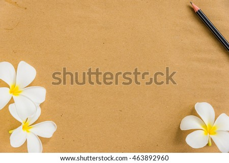 Black pencil and flower on blank brown paper copy space for background user