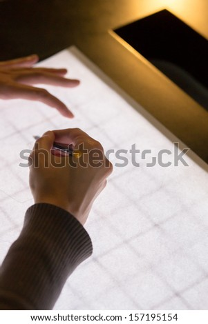 Black pencil in a right hand on white backlight table background, the other hand is holding the paper