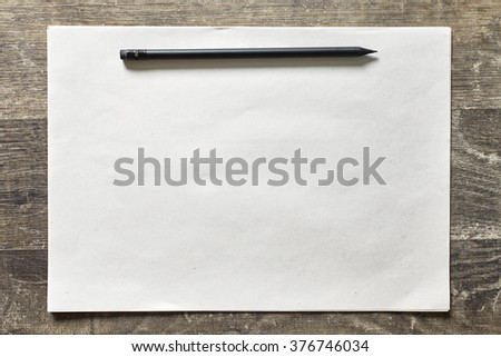 Black pencil on a sheet of paper to the top on a dark wooden background