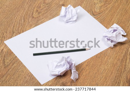 black pencil on clear white paper with crumble paper balls on wooden table background - stock photo