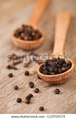 black pepper and cloves in wooden spoons on rustic wooden background - stock photo