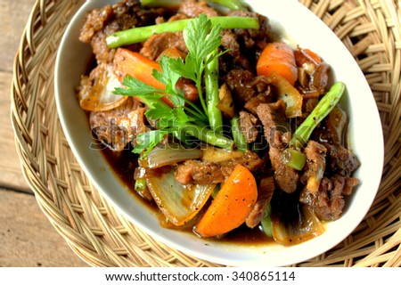 Black Pepper Beef Asian style. Beef cooked with black pepper, bean, onion and carrot. Served on wooden table - stock photo