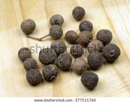 Black pepper corns on cutting board  - stock photo