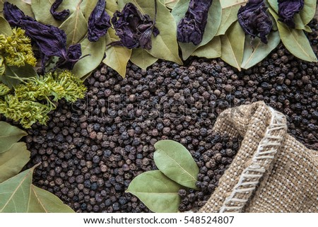 Black pepper grains in the burlap bag on the pepper background with dried bay leaves, purple basil leaves and parsley. Composition of seasoning. Healthy eating and lifestyle.