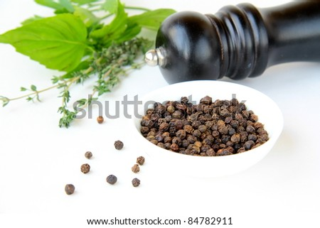 black pepper in a bowl and herbs thyme, basil - stock photo