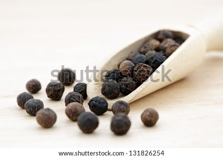 Black pepper  in wooden scoop - stock photo