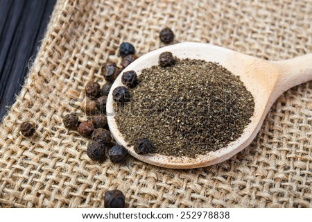 black pepper on the wooden spoon - stock photo