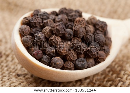 black pepper on wooden spoon - stock photo