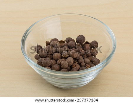 Black pepper seeds on the wood background
