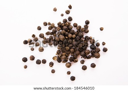 Black pepper seeds on white - stock photo