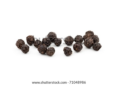 Black peppercorns against a white background