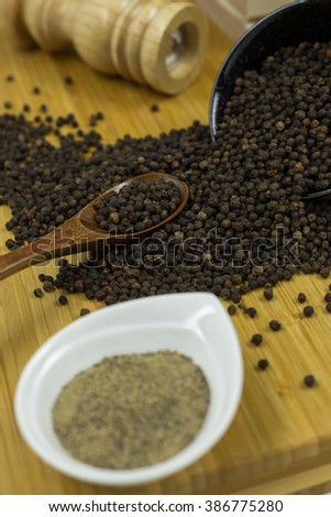 Black peppercorns and Ground pepper - selective focus