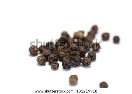 Black peppercorns isolated on white - stock photo