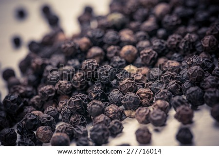Black peppercorns on wooden background - stock photo
