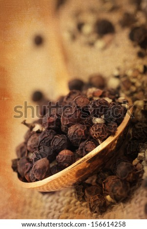 black peppercorns served in a spoon, rustic background texture applied.
