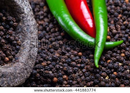Black peppercorns with chili peppers detail - stock photo