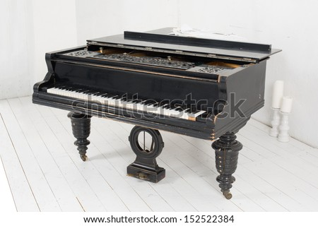 Black piano and two candles in a light room with white walls and floors - stock photo