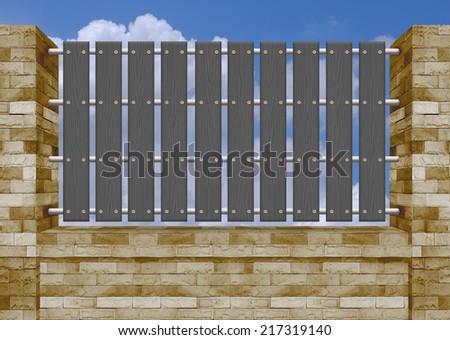 Black picket fence, brick wall. - stock photo
