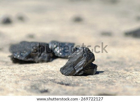 Black pieces of coal lying on the road