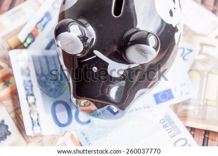 Black piggy bank on a pile of money - stock photo