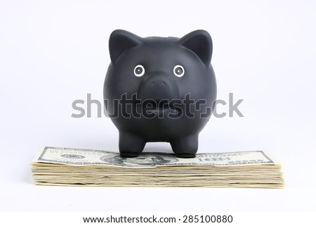 Black piggy bank standing on stack of money american hundred dollar bills on white background Black friday, cyber monday - stock photo