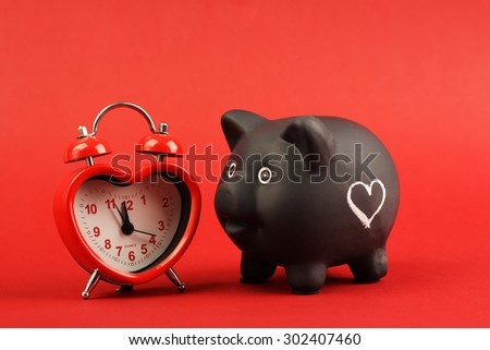 Black piggy bank with white heart and heart alarm clock on red background - stock photo