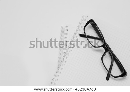 black plastic glasses on the opened notepad