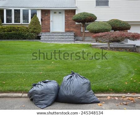Black Plastic Trash Bags suburban home residential neighborhood USA - stock photo