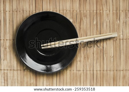 Black plate and wooden chopsticks on bamboo mat as a background - stock photo