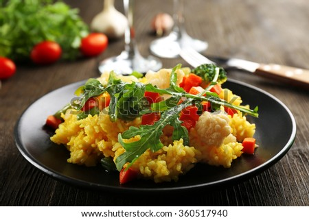 Black plate with vegetable risotto on served wooden table - stock photo
