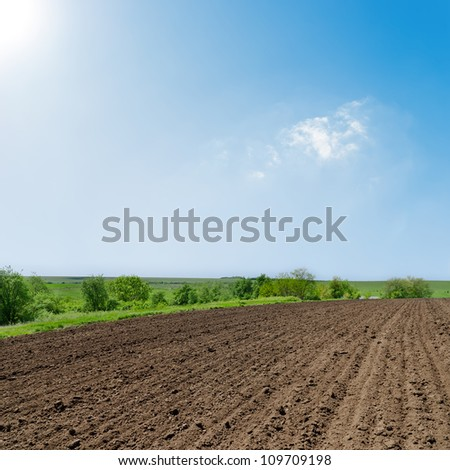 black ploughed field under deep blue sky with sun - stock photo