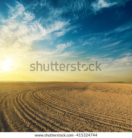 black plowed field in sunset - stock photo
