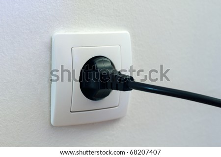 Black plug plugged in a socket. - stock photo
