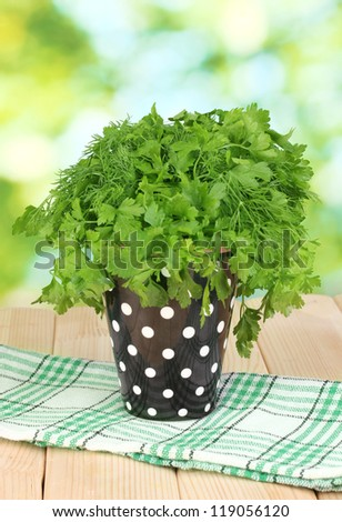 Black pot with parsley and dill on wooden table on natural background - stock photo