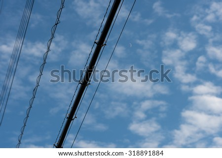 Black Power lines crossing a blue sky dappled with soft clouds and a crescent moon.