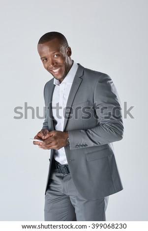 Black professional businessman in suit on his smartphone in studio - stock photo
