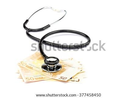 Black professional stethoscope lying on few euro notes isolated on white background - stock photo