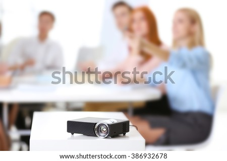 Black projector on white table for business presentation in the foreground - stock photo