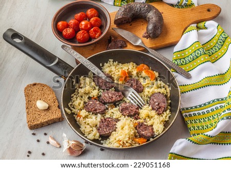 Black pudding with rice in a pan with a slice of garlic and a piece of bread