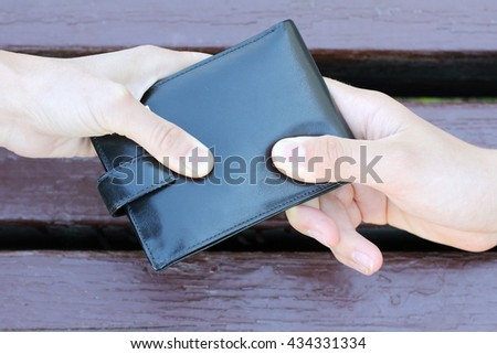 black purse dragging in different directions two human hands / struggle for the purse - stock photo