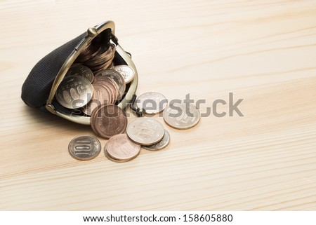black purse with coins on wooden background
