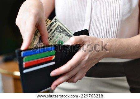 Black purse with money in woman`s hand (soft focus) - stock photo