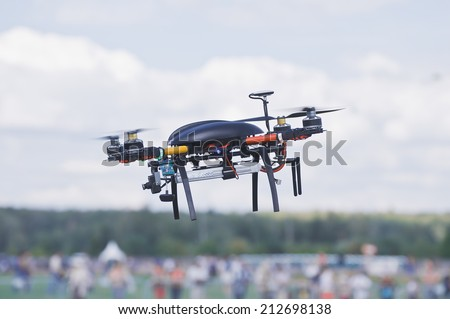 Black quadrocopter above the crowd of people. - stock photo